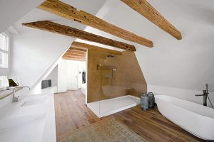 Die alten Holzbalken blieben in dem Bad mit Dachschräge sichtbar.