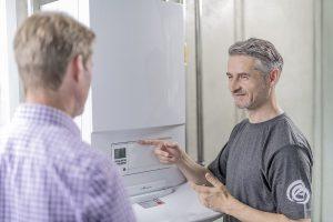 Fachmann informiert den Kunden über Einstellungsmöglichkeiten der Heizungsanlage.